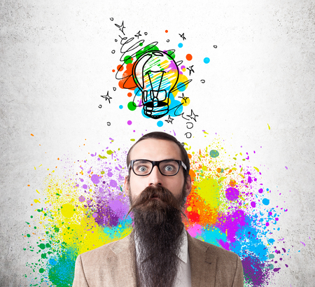 baffled: Baffled man in glasses with long beard is standing against concrete wall with colorful light bulb sketch. He is surrounded by rainbow splashes. Concept of creative idea
