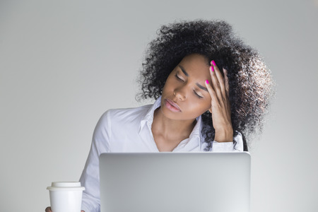 deprivation: Close up of tired office employee sitting at her workplace with laptop in room with gray walls. Concept of sleep deprivation Stock Photo