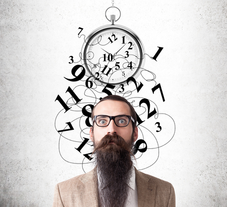 baffled: Baffled man with beard and glasses standing near concrete wall with broken stopwatch on it. Concept of time management gone wrong