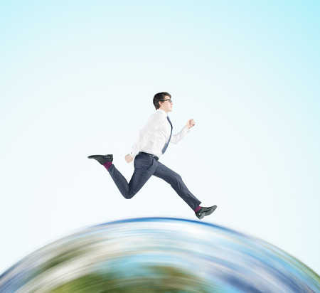 Side view of businessman in glasses running on huge globe. Concept of international business. Mock up. Stock Photo