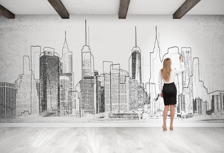 rear view girl: Rear view of woman drawing and standing near concrete wall with cityscape sketch on it. Concept of city planning. 3d rendering.