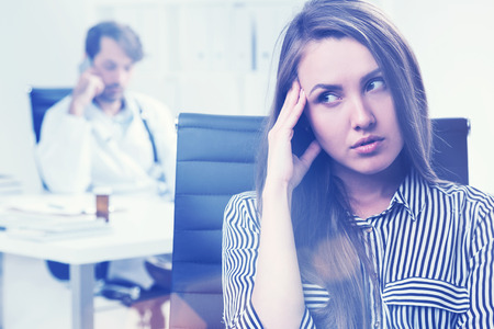 pissed off: Portrait of woman who is pissed off because her doctor is talking on the phone and ignoring her. Tond image