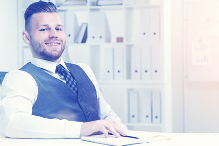 broadly: Young office worker sitting at his table and smiling broadly to camera in office room with binders on shelves and white board. Concept of work. Toned image