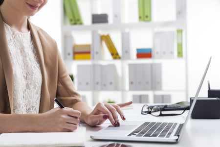 Side view of smiling woman in beige cardigan typing and writing simultaneously. Concept of doing two task and not succeeding