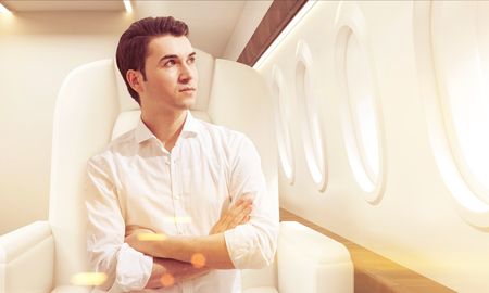 concentrate: Portrait of young businessman sitting in business class of a plane with his arms crossed. Concept of success and luxury. Toned image. 3d rendering. Stock Photo