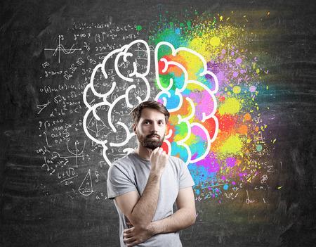 Homme barbu en T-shirt debout près d'esquisse de cerveau géant sur tableau noir. Concept de logique et de sens Banque d'images - 65144361