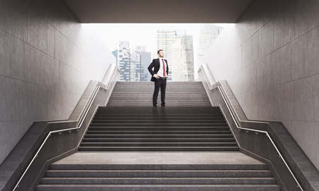 Portrait of businessman standing with his hands on the waist on the stairs leading to city street. Concept of good prospects. 3d rendering.