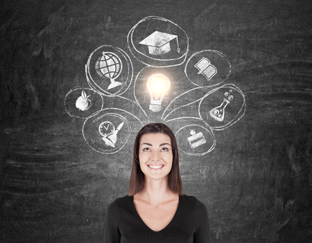 postgraduate: Smiling woman in black is standing near chalkboard with education icons on it. Concept of knowledge gaining