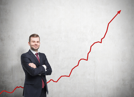 Portrait of man in black standing against concrete wall with growing graph on it. Concept of successful firm. Mock up Stock Photo