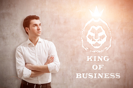 Young man in white shirt standing near concrete wall with king of business sketch on it. Concept of true leader. Toned image