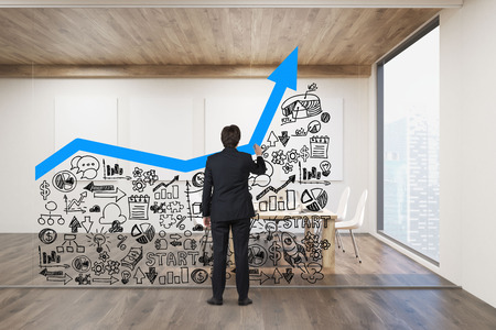 drawing large: Rear view of businessman drawing large blue graph and small business icons on glassboard in office. Concept of the right business strategy. Mock up. 3d rendering. Stock Photo
