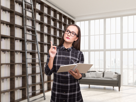 Nerdy girl in glasses is standing with a book in her house library. Concept of science and education. 3d rendering Stock Photo