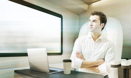 compartment: Young man travelling in a modern train. Laptop and coffee cup are standing on the compartment table. Concept of business trip. 3d rendering. Mock up