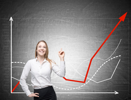Blond woman with her finger in the air is standing near blackboard with red and white graphs. Concept of good idea