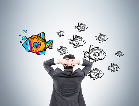 Rear view of businessman looking at fish sketches on gray wall. One fish is big, colorful and swimming in different direction. Concept of original approach