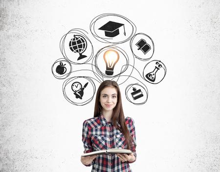 Sonriente niña nerd con un libro está de pie cerca de la pared de hormigón con iconos de educación negro. Concepto de la importancia del conocimiento