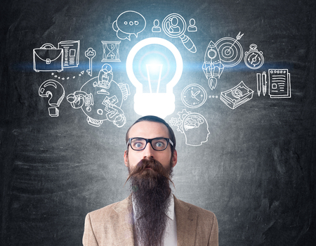 Baffled man with long beard is standing near chalkboard with blue light bulb and project sketches on it. Concept of new business idea. Toned image