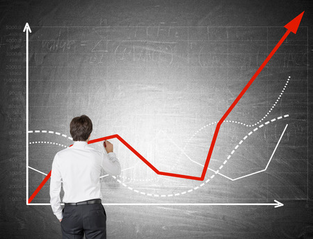 Rear view of businessman in white shirt drawing a graph on chalkboard. Concept of statistician's work Foto de archivo