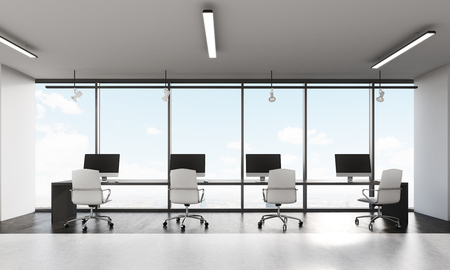 pc: Front view of row on computers on long desk in office with panoramic windows. Concept of open office. Stock Photo