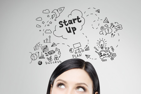 starting a business: Close up of womans head with project launch icons drawn above her on gray wall. Concept of starting small business Stock Photo
