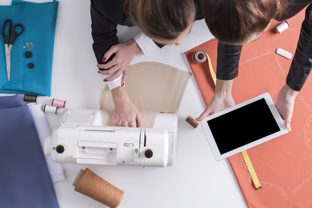 made to measure: Top view of two women sewing together. One is sitting at a sewing machine. The second is holding a tablet and showing it to her colleague. Mock up