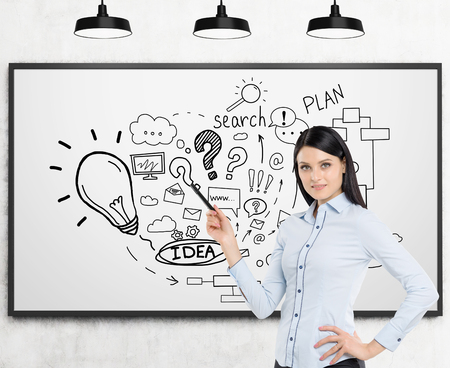 black haired: Smiling black haired woman with pen is standing near whiteboard with startup idea sketch on it. Concept of business education