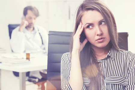 pissed off: Portrait of a woman who is pissed off because her doctor is talking on the phone and ignoring her. Tond image Stock Photo