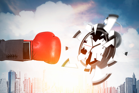 Businessmans hand in red boxing glove is smashing giant alarm clock against cityscape background. Concept of deadline. Toned image