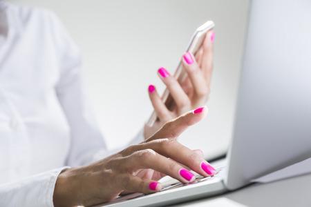 スマート フォンを押し、ノート パソコンのキーボードで入力のアフリカ系アメリカ人の女性の手のクローズ アップ。マルチタスクの概念 写真素材