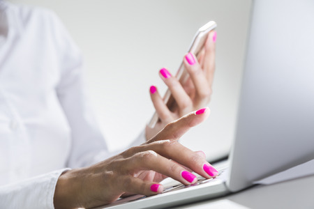 Close up of African American woman's hands holding smartphone and typing at laptop keyboard. Concept of multitasking