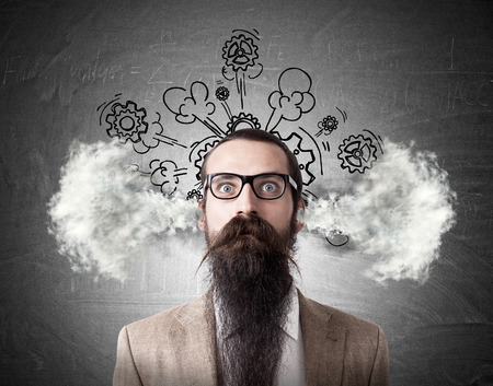 baffled: Portrait of baffled man with long beard and steam going out of his head. Sketch with cogs is drawn on the blackboard behind him. Concept of frustration Stock Photo
