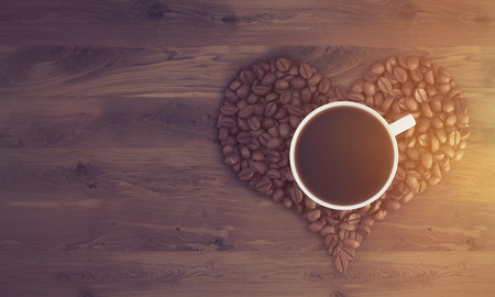 liking: Top view of cup of coffee standing on coffee beans shaped like a heart on wooden table. Concept of liking coffee. 3d rendering. Mock up. Toned image Stock Photo
