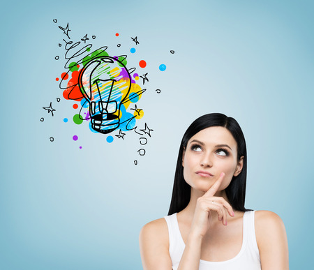 business mind: Close up of girl in white tank top looking at colorful light bulb sketch drawn on blue wall. Concept of good idea