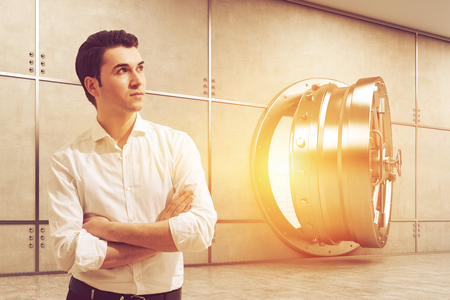 storing: Young man in white shirt is standing near open bank vault. Concept of banking and storing your valuable stuff. Toned image. 3d rendering Stock Photo