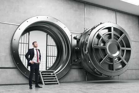 near: Confident businessman is standing near wide open vault door. Concept of money saving. 3d rendering. Stock Photo