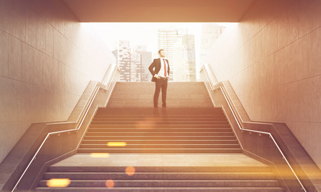Portrait of businessman standing with his hands on the waist on the stairs leading to city street. Concept of good prospects. Toned image. 3d rendering.