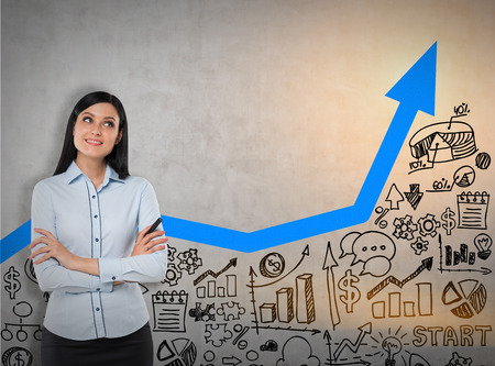 Smiling woman with black hair is standing near concrete wall with blue graph and business sketches. Mock up. Toned image Stock Photo
