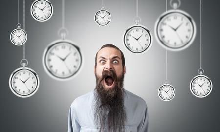 Gridare uomo con la barba lunga è in piedi vicino alla parete grigia. Molti orologi sono appesi intorno a lui. Concetto di gestione del tempo.