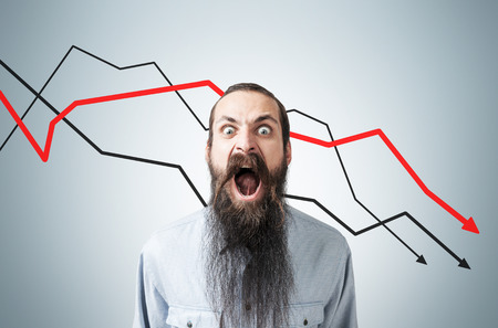 Shouting man with long beard is standing near gray wall with three declining graphs. Concept of crisis Reklamní fotografie