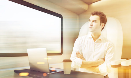compartment: Young man travelling in a modern train. Laptop and coffee cup are standing on the compartment table. Concept of business trip. 3d rendering. Mock up. Toned image Stock Photo