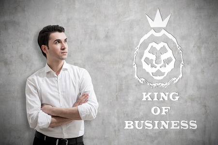 Young man in white shirt standing near concrete wall with king of business sketch on it. Concept of true leader.