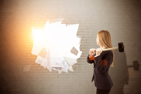 finding your way: Woman is smashing wall with sledgehammer. Large city panorama is seen in the distancel. Concept of finding your way in business. Toned image