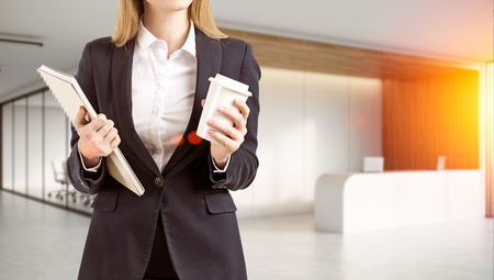 toning: Close up of an office employee holding a cup of coffee and a large notebook while standing in a lobby near a reception counter. 3d rendering. Mock up. Toned image