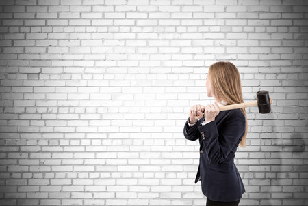 Side view of blond woman with sledgehammer about to smash white brick wall. Concept of no limits. Mock up Stock Photo