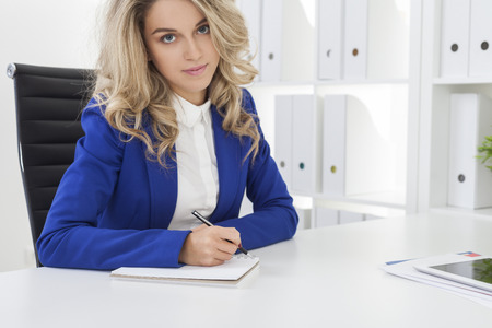 Beautiful woman in blue blazer with blond hair who is taking notes in her office