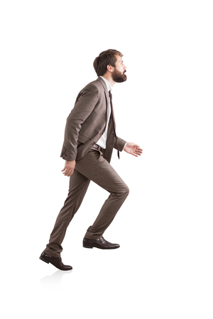 Side view of a bearded businessman climbing an invisible ladder. Concept of success and career growth. Isolated Stock Photo
