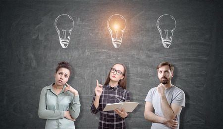 bocetos de personas: Three people are standing near a blackboard. There are light bulb sketches above their heads. One is glowing. Concept of brainstorming