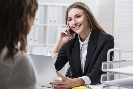 Smiling businesswoman is on her phone and holding her laptop. Candidate for the vacant position in the company is sitting in the office