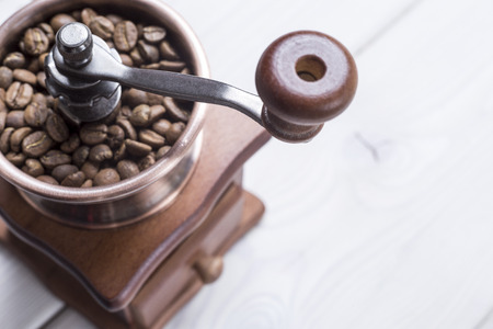 Close up of a coffee grinder standing on a wooden table. Concept of making your own coffee. Stock Photo