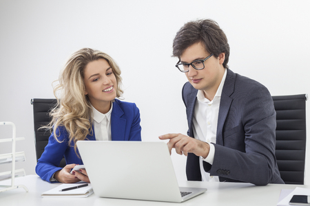 conversing: Guy wearing glasses is showing some details to his colleague at his laptop screen. She seems really interested